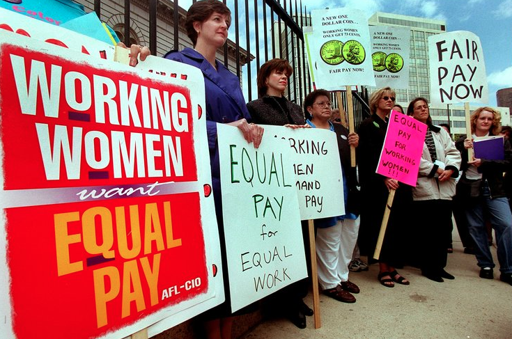 Women hold signs demanding Equal Pay for Equal Work