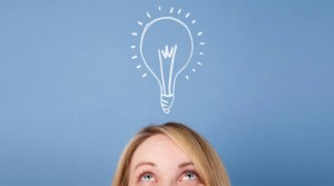 [This image features the top half of a woman's face as she looks upward at a sketched light bulb.]