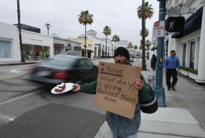 David Lowe, 37, a homeless man, holds a sign as he offers a plate of cupcakes during May Day demonstrations in Beverly Hills, California May 1, 2012. REUTERS/Lucy Nicholson (UNITED STATES - Tags: CIVIL UNREST)